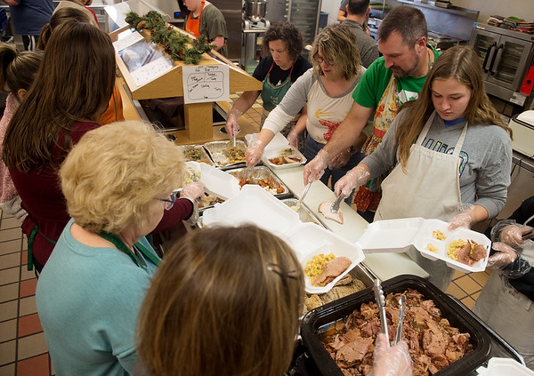 Volunteers assemble delivery meals on Wednesday at the Carthage Crisis Center. The center delivers over 100 meals on Christmas Day.<br /> Globe | Roger Nomer