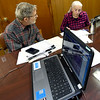 From the left: Elliott Denniston and Penny Hagedorn work on voter outreach as they listen to the impeachment proceedings on Wednesday at the SWMO Democrats headquarters.<br /> Globe | Laurie Sisk