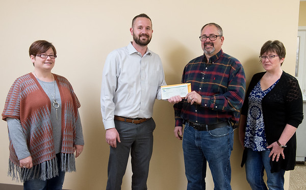 (from left) Tracy Tune, operations manager with Joplin Workshops, Scott Sullivan, manager of business and community development with Liberty Utilities, Jeff Jones, executive director of Joplin Workshops, and Lori Owens, controller with Joplin Workshops, proceed with the donation of $1,000 from Liberty to the Joplin Workshops on Giving Tuesday at the workshop. The money will help the workshop purchase a forklift.<br /> Globe | Roger Nomer