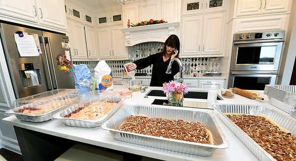 Krista Asbell multitasks in her Carl Junction home with phone calls and baking pecan and cherry pies for about 200 guests for their annual community Christmas dinner at the Carl Junction Community Center.<br /> Globe | Laurie Sisk