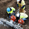 Globe/T. Rob Brown<br /> Missouri-American Water utility workers, clockwise from left, Justin Minson, Matt Andrews and Roland Tucker operate a water main tapping tool Friday afternoon at the intersection of 28th Street and Bird Avenue in Joplin.