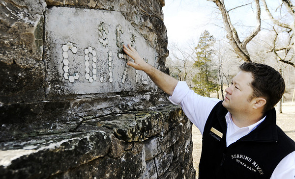 Globe/T. Rob Brown<br /> Dusty Reid, Roaring River State Park superintendent, touches  a stone on a fireplace built by CCC workers during a tour Thursday, Feb. 16, 2012, at the historic park near Cassville.