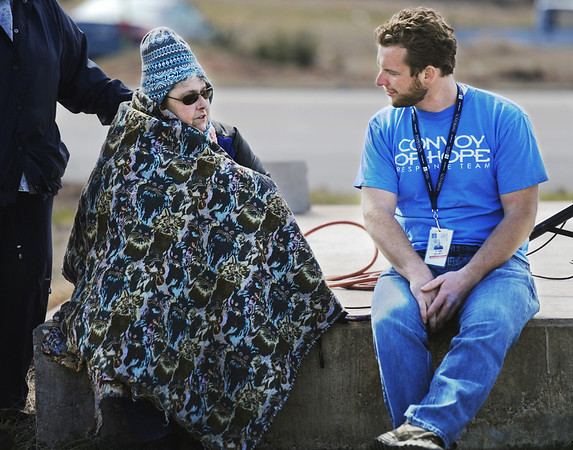 Globe/T. Rob Brown<br /> Shirley Ellis, sister-in-law of Helen Owen, keeps bundled as she speaks with Ryan Grabill, disaster services coordinator with Convoy of Hope, just before the announcement that the organization plans to build 12 new homes in Joplin for residents who lost homes to the May 22, 2012, tornado. The announcement was made Monday morning near the intersection of 26th Street and Bird Avenue.
