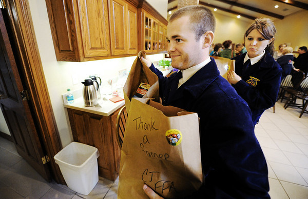"Globe/T. Rob Brown<br /> Carl Junction High School FFA seniors Benny McWilliams, president, and Mickelle Gibson, vice president, carry in groceries donated through the Missouri Farm Bureau to the Ronald McDonald House pantry Wednesday morning, Feb. 8, 2012, in Joplin. The donation was part of the Farm Bureau's ""Thank a Farmer"" week (Feb. 5-11)."