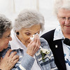 Globe/T. Rob Brown<br /> Resident Bonnie Betz, center, cries as she recalls her experience the day of May 22, 2011, as Sister Lillian, CEO Mercy Housing Inc, holds the microphone and Margaret Hanschu comforts Betz Tuesday morning, Feb. 21, 2012, during the grand re-opening of Mercy Village in Joplin.