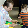 Globe/T. Rob Brown<br /> Justin Thomas, owner of the Wild Flower, looks at a children's book with three-year-old Ethan, who is autistic, after Thomas presented a check for $6,500 to the Ozark Center for Autism Thursday afternoon, Feb. 2, 2012, at the Ozark Center for Autism in Joplin.