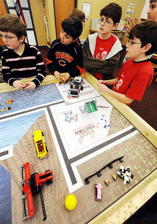 Globe/T. Rob Brown<br /> Roboteers (from left) fourth-graders Logan Williams and Layne Henning, seventh grader Ian Lawson and fifth grader Eli Lawson look over the mission zones for Robbie the robot Wednesday after school, Feb. 8, 2012, at Seneca Intermediate School.
