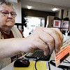 Globe/T. Rob Brown<br /> Election Judge Lucille Myers, of Carl Junction, uses a new voter registration computer system to scan a voter's driver's license at First Christian Church of Carl Junction Tuesday morning, Feb. 7, 2012.