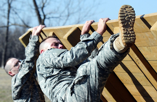Globe/T. Rob Brown<br /> Sgt. 1st Class Brandon Stockwell, of Brunswick, climbs over an incline wall Tuesday morning, Feb. 28, 2012, on an Army National Guard obstacle course at Camp Crowder in Neosho. About 200 soldiers started their air assault training. Spc. Robert Tabor, left, of Springfield, also begins his climb.