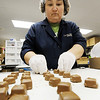 Globe/T. Rob Brown<br /> Michelle Rowan, production line employee with the Candy House, picks up caramel-filled chocolates off a conveyor belt Monday afternoon, Feb. 20, 2012, at the Joplin chocolate factory.