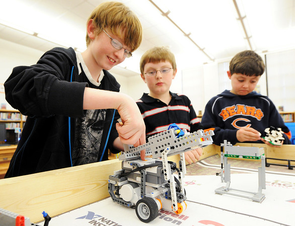 Globe/T. Rob Brown<br /> Dallas Williams, sixth grader, starts up a robot Wednesday after school, Feb. 8, 2012, at Seneca Intermediate School, as foruth graders Logan Williams and Layne Henning look on.