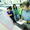 Globe/T. Rob Brown<br /> Carthage Junior High School seventh grade physical science teacher Craig Kyte grades a science fair project on leaking diapers by Yocelyn Flores (not pictured) as Flores' classmates, from left, Gregoria Cancinos, Yennifer Lopez-Gonzalez and Darlin Borrayes-Reyes look on Wednesday afternoon, Feb. 22, 2012, in the school's gymnasium. The school expects to have between 600 and 650 science fair boards in a competition where the best 20 will advance to regional competition at Missouri Southern State University in March.