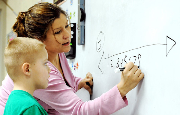 Globe/T. Rob Brown<br /> Student teacher Ashley E. Cook, of Joplin, who is an MSSU elementary education major, writes a mathematics example on the board for first grader James Gandy Wednesday afternoon, Feb. 15, 2012, at Spring Grove Elementary School in Galena, Kan.