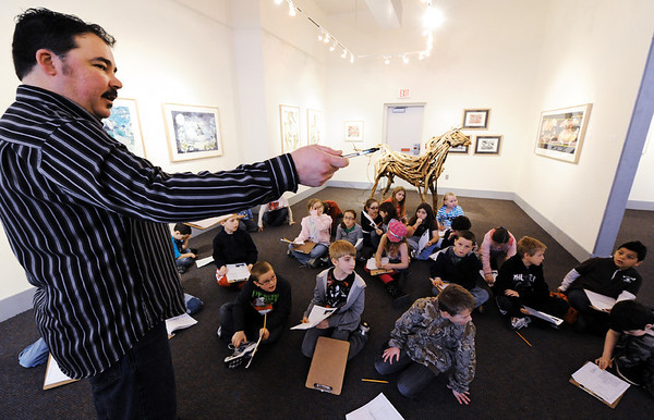 Globe/T. Rob Brown<br /> Shaun Conroy, Spiva Center for the Arts gallery and gift shop coordinator, speaks with a group of Columbia Elementary School third graders, about Rachel Wilson's found wood sculptures of horses on display at Spiva Center for the Arts Tuesday afternoon, Jan. 31, 2012.