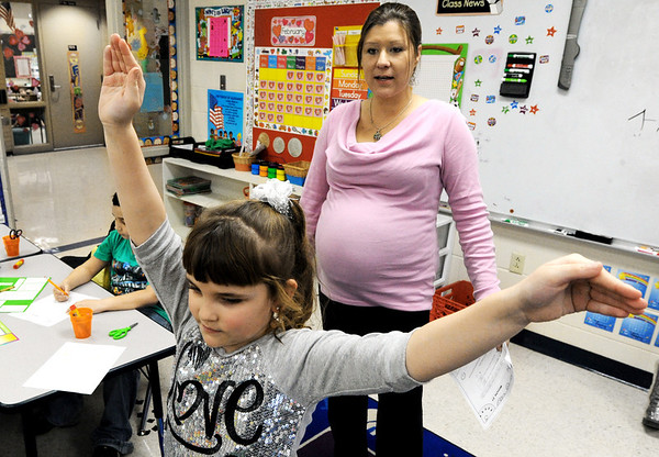 Globe/T. Rob Brown<br /> Kensi Holden, a Spring Grove Elementary School first grader, holds her arms in the shape of 2 o'clock, as quized Wednesday afternoon, Feb. 15, 2012, by student teacher Ashley E. Cook, of Joplin, who is an MSSU elementary education major. The school is part of the Galena, Kan., district.