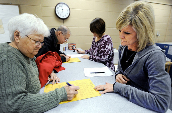 Globe/T. Rob Brown<br /> Darlene LaGasse, left, of Joplin, and her husband, Louis, sign up to vote absentee ballot Friday afternoon, Feb. 3, 2012, in the Jasper County Clerk's Office at the Joplin Courts Building. Jasper County Deputy Clerks Susan Moore, right, and Terri Dawald, both of Carthage, assist the couple.