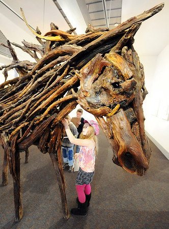 Globe/T. Rob Brown<br /> Charity Persinger, a Columbia Elementary School third grader, touches a found wood sculpture of a horse at Spiva Center for the Arts Tuesday afternoon, Jan. 31, 2012. Students on a field trip visited the gallery to see Rachel Wilson's sculptures and other horse-themed art pieces such as collages, etchings and monoprints.