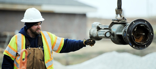Globe/T. Rob Brown<br /> Missouri-American Water utility worker Matt Andrews guides a water main tapping tool, attached to a hoist, Friday afternoon, as a team taps a water main at the intersection of 28th Street and Bird Avenue in Joplin.