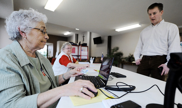 Globe/T. Rob Brown<br /> Supervisory Election Judge Ruth Elliston, checks voter registration for James Billings as Election Judge Lucille Myers, all of Carl Junction, looks on at First Christian Church of Carl Junction Tuesday morning, Feb. 7, 2012. The election judges for Precincts 1 and 2 in Carl Junction said they were having low turnout.
