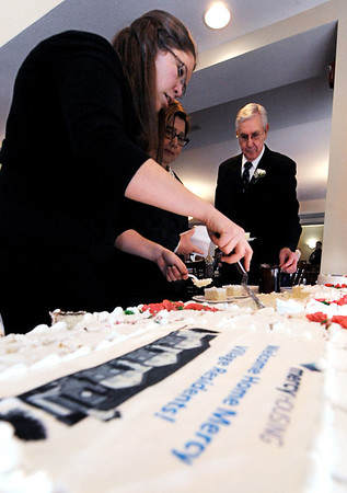 Globe/T. Rob Brown<br /> Kate Hurt, left, regional manager of resource development for Mercy Housing, and Boyd Crook, key holder for Mercy Village, cut and deliver pieces of cake to residents Tuesday morning, Feb. 21, 2012, during the grand re-opening of Mercy Village in Joplin.