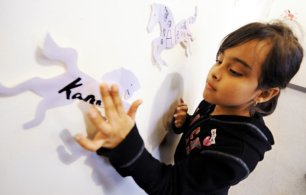 "Globe/T. Rob Brown<br /> Karen Alvarado, a West Central Elementary School third grader, places a paper horse, decorated with her name, on the wall in the ""secret room"" at Spiva Center for the Arts Tuesday afternoon, Jan. 31, 2012."