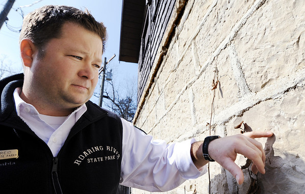 Globe/T. Rob Brown<br /> Dusty Reid, Roaring River State Park superintendent, examines chisel marks on Cabin 1 built by CCC workers during a tour Thursday, Feb. 16, 2012, at the historic park near Cassville.