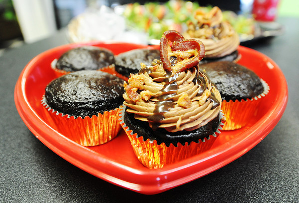 Globe/T. Rob Brown<br /> A completed bacon cupcake surrounded by future bacon cupcakes Tuesday morning, Feb. 12, 2013, at Sweet Designs Cakery, owned by Heather Horton, 311 N. Broadway in downtown Pittsburg, Kan.
