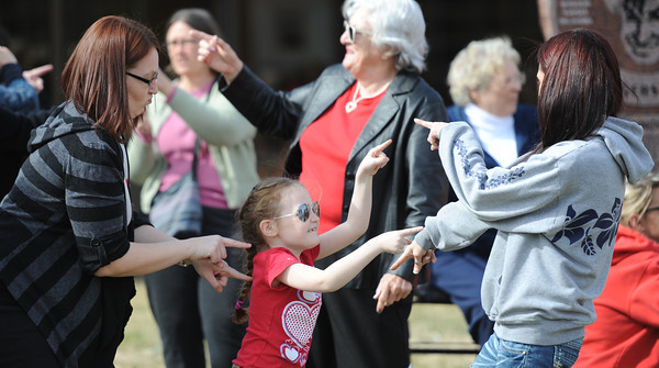 Globe/T. Rob Brown<br /> Ellaryn Hall, 7, of Joplin, takes center of part of a group of women in a dance for the international Billion Rising event in front of the Joplin Public Library Thursday afternoon, Feb. 14, 2013. From left, her mother, Marlena Hall points at her while her aunt Charity Hall of Pittsburg, Kan., does likewise at right.
