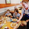 Globe/T. Rob Brown<br /> Charlotte Stickrod, a server with IHoP (International House of Pancakes), delivers a few shortstacks to the table for 1-year-old Conley Sprouls, right, son of Morgan Sprouls, far left, of Joplin, as her other son Carson Johnson, 4, and the boys' great grandmother Beryl Nickolaisen get ready to dig into their shortstacks Tuesday morning, Feb. 5, 2013. The Joplin restaurant was offering free shortstacks to customers with donations to Children's Miracle Network Hospitals.