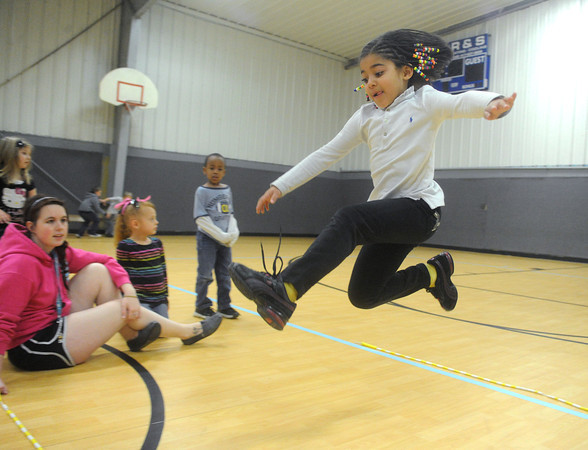 Globe/Roger Nomer<br /> Tieshia Sanders, 7, takes a running jump during a game of Jump the River at the Boys and Girls Club on Monday.