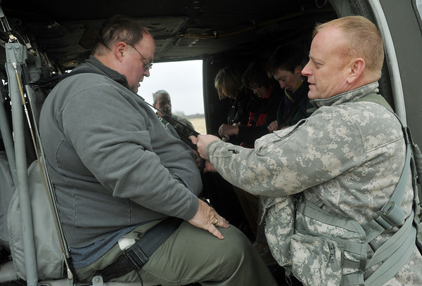 Globe/Roger Nomer<br /> Sgt. First Class Daryl Kelley helps Rod Anderson, a member of the Missouri Southern Board of Governors, buckle into the Black Hawk helicopter on Wednesday.