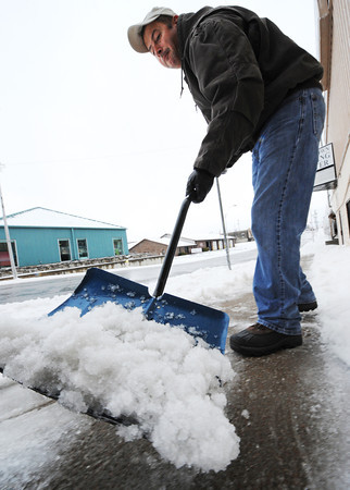 Globe/T. Rob Brown<br /> Bob Maus, a delivery driver for State Beauty Supply shovels ice and snow Thursday afternoon, Feb. 21, 2013, in front of the entrance to the business in the 500 block of South Virginia Avenue.