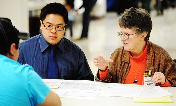 Globe/T. Rob Brown<br /> Immigration attorneys Suzanne Gladney, right, Ron Nguyen speak with an immigrant as he fills out legal documents Monday afternoon, Feb. 4, 2013, at Pittsburg (Kan.) Memorial Hall.