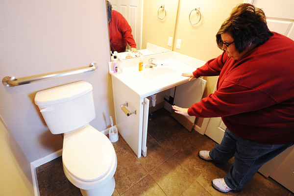 Globe/T. Rob Brown<br /> April Sidenstricker shows important accessibility options in her home such as an opening under the sink and handrails around the toilet Friday morning, Feb. 8, 2013.