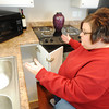 Globe/T. Rob Brown<br /> April Sidenstricker shows one of the accessibility options in her home Friday morning, Feb. 8, 2013. By having an opening under the kitchen sink, she can easily access the sink, microwave, oven and refrigerator from that seated position.