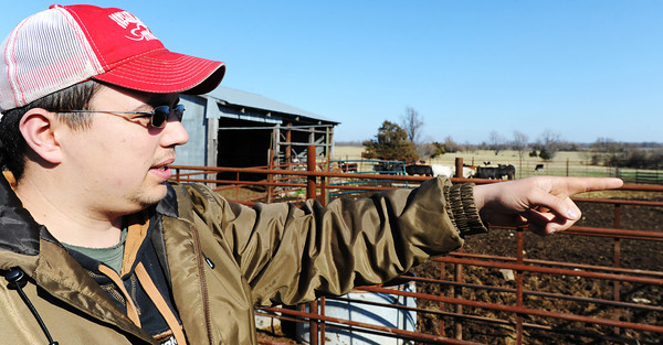 Globe/T. Rob Brown<br /> Kyle Burk, of Marionville, points out places where cattle rustlers trespassed, damaged his property and stole most of a herd of cattle recently while surveying his replacement herd Wednesday afternoon, Feb. 13, 2013.