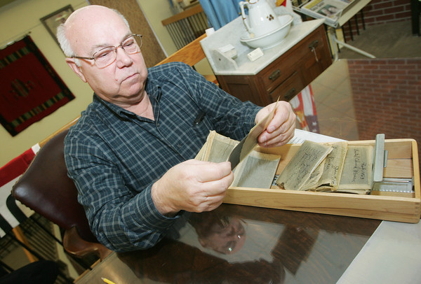 Globe/Roger Nomer<br /> Larry Roberts, president of the Ottawa County Historical Society, looks through negatives at the Dobson Museum for use in an upcoming mining documentary.