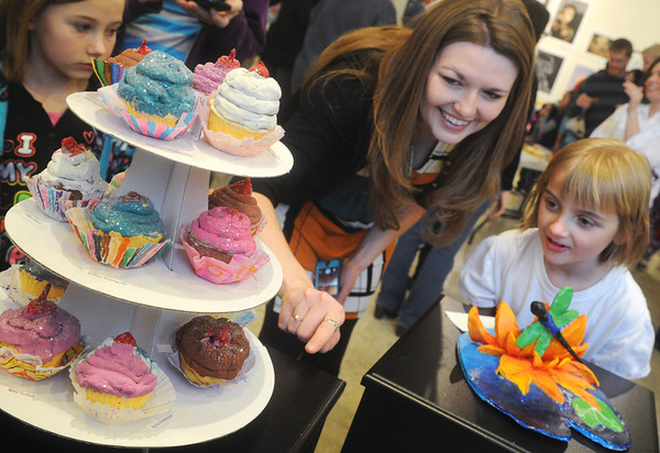 Globe/Roger Nomer<br /> Webster Elementary art teacher Amber Davidson helps Katlynn Allee, a second grader at Webster, find her cupcake on display at the Missouri Art Education Association District 9 (K-12) Art Show at Missouri Southern's Spiva Art Gallery on Saturday.  The exhibit features select artwork from students in Carl Junction, Carthage, Diamond, Joplin, Monett, Neosho and Webb City, and runs through this Friday.