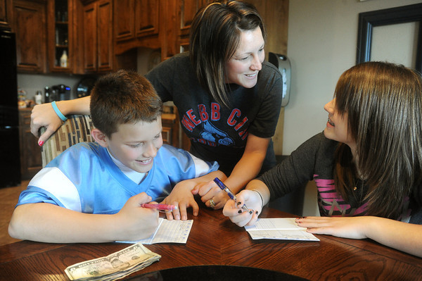 Globe/Roger Nomer<br /> Keaton Neil, 10, and Kayden Baker, 12, get help from their mom, Heather Wade, as they fill out their debit books.