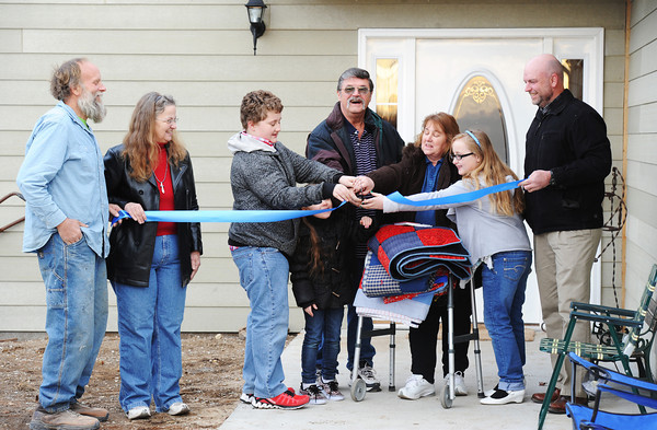 Globe/T. Rob Brown<br /> The Bill and Luann Lett family cut the ribbon to their new home Wednesday evening, Feb. 20, 2013. Mike and Dawn Aalbers, left, and Dave Brown, right, ruling elder of Christ the King Presbyterian Church, look on. The home was one of more than 60 homes completed by Rebuild Joplin as part of its 100-home goal.
