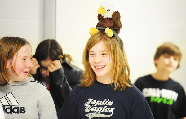 Globe/T. Rob Brown<br /> Joplin South Middle School sixth grader Hera Schneider wears a stuffed toy of an eagle on her head Thursday afternoon, Feb. 7, 2013, as she and classmates walk down the school hallways to an assembly.