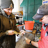 Globe/T. Rob Brown<br /> Step 5: Roaring River State Park Fish Hatchery's Brad Farwell, assistant hatchery manager, left, aims the flow of a male trout's genetic material into a series of three vials held by resource assistant Dustin Back.