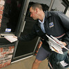 Globe/Roger Nomer<br /> Shane Miller delivers mail along his route on Main Street on Thursday afternoon.
