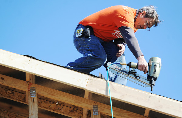 Globe/T. Rob Brown<br /> Dan Helmich, construction supervisor with Samaritan's Purse, attaches a roof liner to a home in the 2500 block of South Virginia Avenue. Helmich said the roofers would be along soon to apply the shingles.