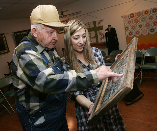 Globe/Roger Nomer<br /> Billie Crawford points out younger self in an old mining photo for Ana Pierce before an interview on Monday at the Dobson Museum.