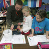 Globe/Roger Nomer<br /> Daniel Osborne looks over Gracie Buchanan, center, fourth grade, and Addy Primm's science project during class at Jasper Elementary on Thursday.