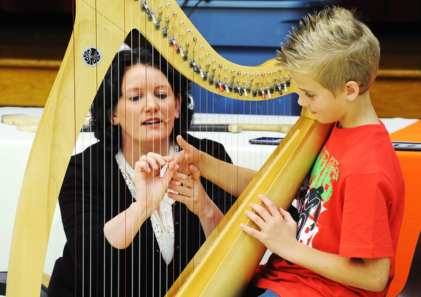 Globe/T. Rob Brown<br /> Kelsey Norman Elementary School fourth grader Damion Schertzer learns to play the harp from Dearbhail Finnegan with the Irish Kaleidoscope, sponsored by ProMusica, Friday afternoon, Feb. 8, 2013, at the school's multipurpose room.
