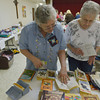 Globe/Roger Nomer<br /> Susan Griffith, Carthage, left, and Janice Bennett, Riverton, look over a book exchange at the montly meeting of the Joplin Area Town and Country Quilters at First Presbyterian Church on Tuesday.