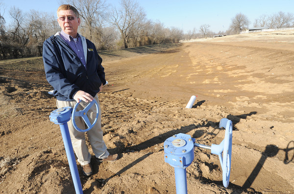 Mark Grigsby, math and science chair at Northeastern Oklahoma A&M, stands near the main retention pond of a new wetland area under construction on the NEO campus.<br /> Globe | Laurie Sisk
