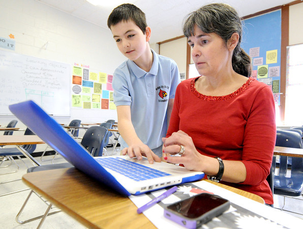 Webb City Junior High School seventh grader Chase Pittman teaches grammar and writing teacher Phyllis Dolence the ins and outs of Popcorn Maker, a video editing software program on Friday at the school. Pittman is one of more than 20 e-leaders at the school.<br /> Globe | Laurie Sisk
